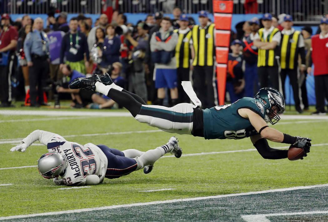 El ala cerrada de los Philadelphia Eagles Zach Ertz (86) se lanza a la zona de anotación sobre Devin McCourty (32) para un touchdown, durante la segunda mitad del partido de fútbol NFL Super Bow ...