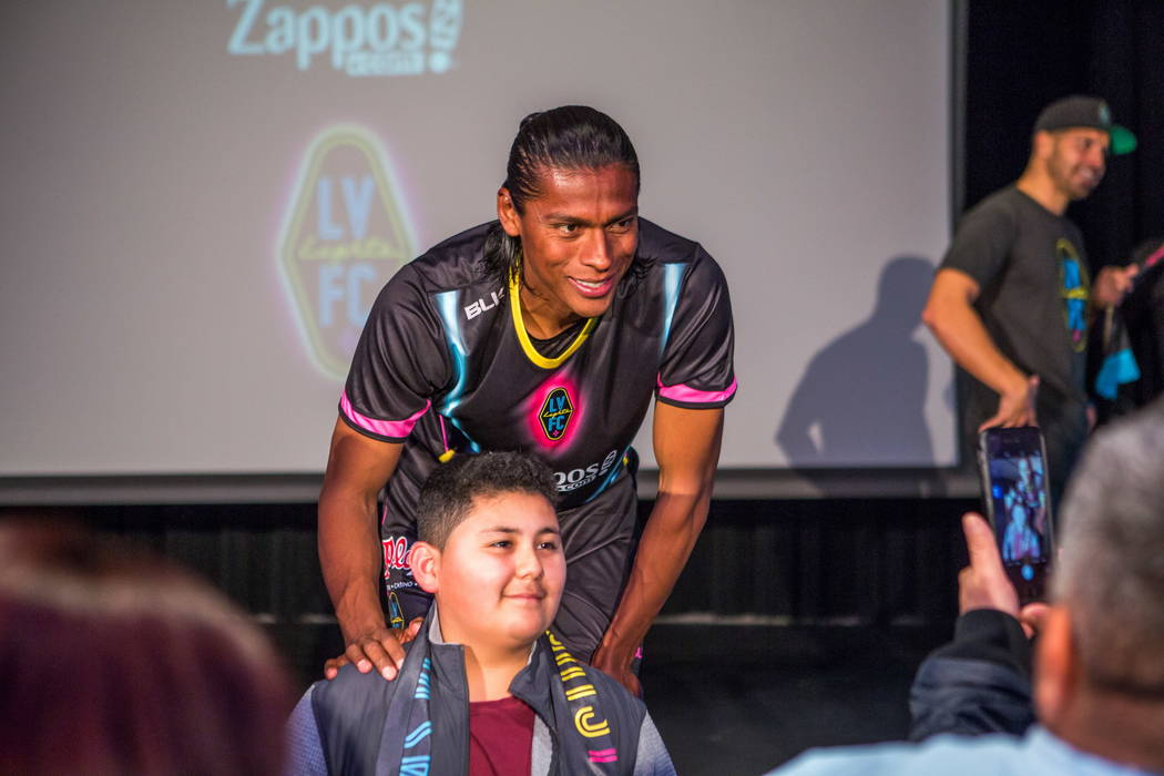 A Joel Huiqui le toman una foto con un fan durante la revelación de la nueva camiseta para el equipo de fútbol de Las Vegas Lights FC en el campus de Zappos Downtown en Las Vegas Boulevard el mi ...