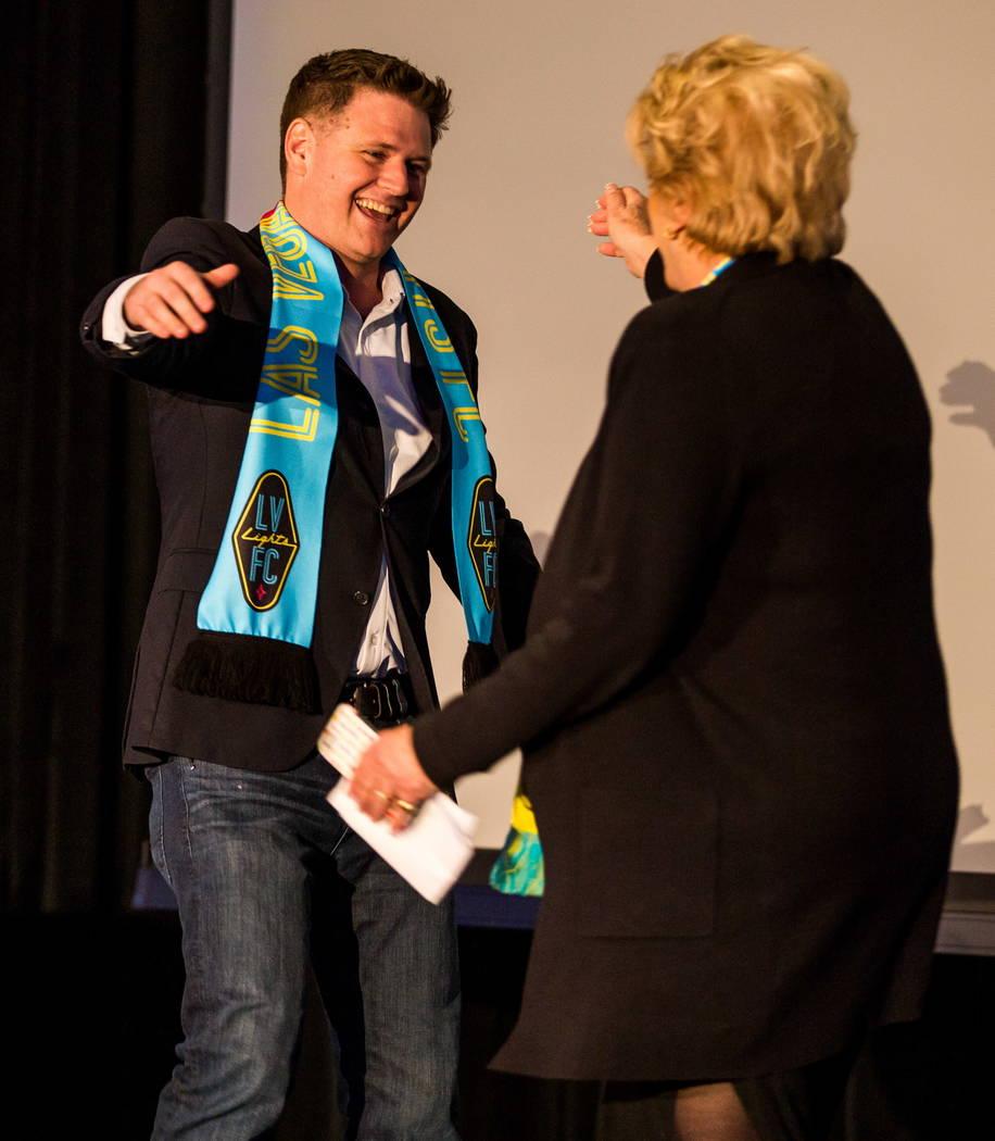 El propietario del equipo de fútbol de Las Vegas Lights FC: Brett Lashbrook, y la alcaldesa Carolyn Goodman se saludan durante el evento de revelación de camisetas en el campus de Zappos Downtow ...