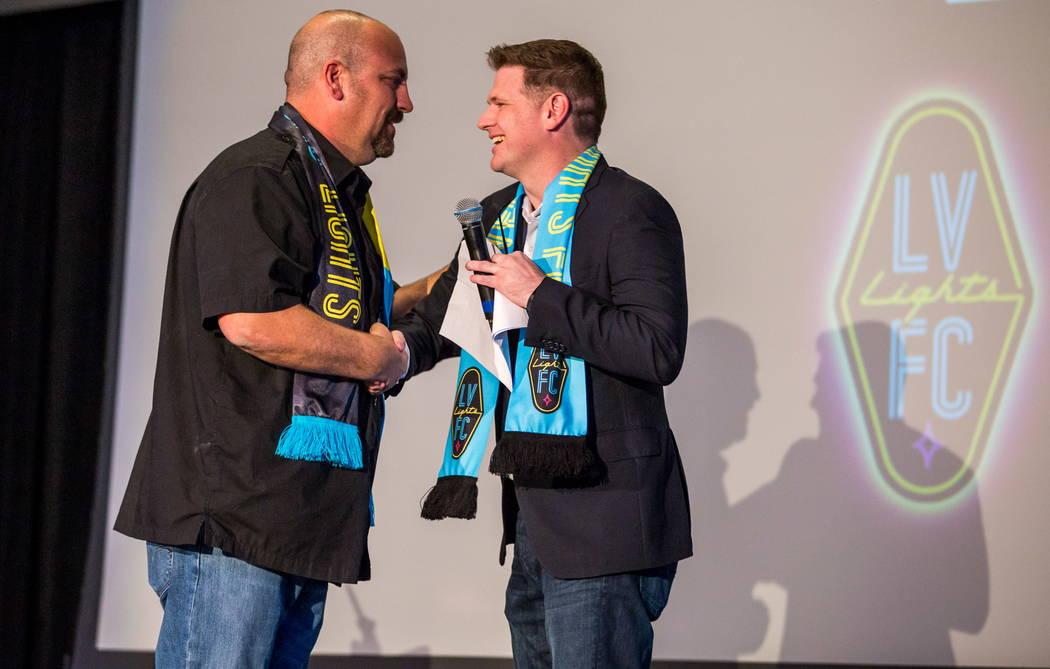 El propietario del equipo de fútbol de Las Vegas Lights FC, Brett Lashbrook, da la mano a Loren Becker, Gerente de Zappos Experience y Community Team, durante el evento de revelación de camiseta ...