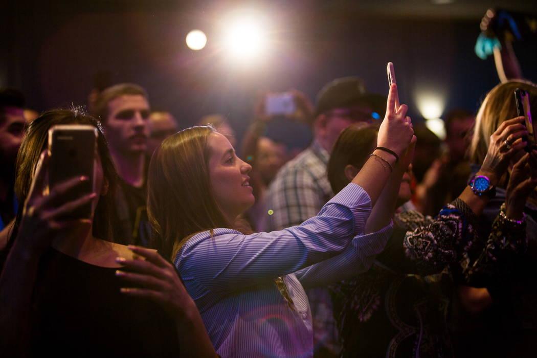 Los fanáticos toman fotos desde los asientos de la audiencia durante la revelación del nuevo jersey para el equipo de fútbol Las Vegas Lights FC en el campus de Zappos Downtown en Las Vegas Bou ...