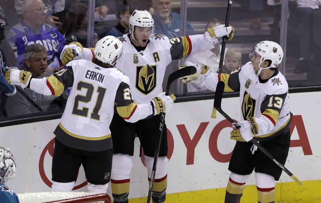Brayden McNabb de Vegas Golden Knights, centro, celebra su gol con sus compañeros Cody Eakin, izquierda, y Brendan Leipsic durante el tercer periodo de un partido de hockey de la NHL contra los S ...