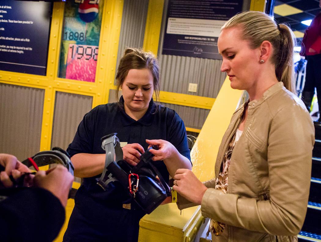 Brittany Coleman, del centro, ayuda a Amanda Lewis de West Palm Beach, Florida, con sus gafas de realidad virtual en la Big Apple Coaster en el New York-New York, Las Vegas, el miércoles 7 de feb ...