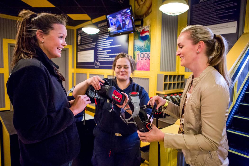 Brittany Coleman, del centro, ayuda a Amanda Lewis, a la derecha, y Ashley Day de West Palm Beach, Florida, con sus gafas de realidad virtual en la Big Apple Coaster en el New York-New York, en La ...