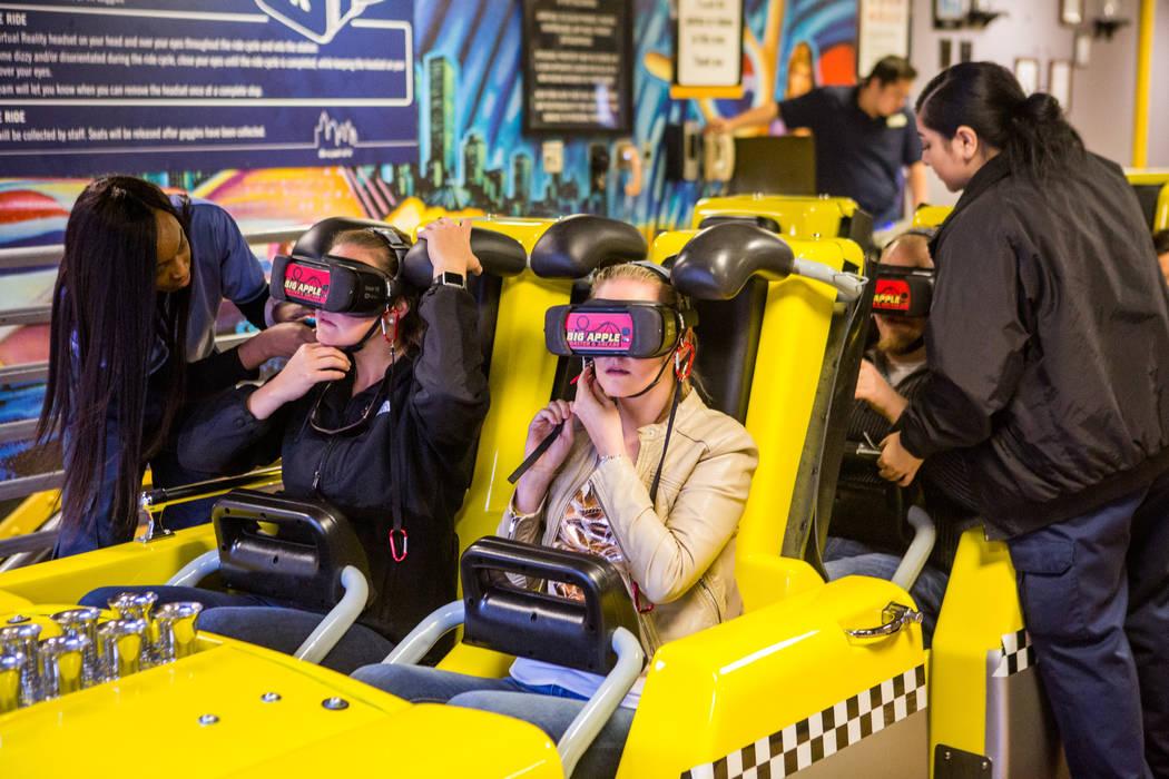 Amanda Lewis, centro derecha, y Ashley Day, centro izquierda, de West Palm Beach, Florida, se preparan para viajar en la Big Apple Coaster con gafas de realidad virtual en New York-New York en Las ...