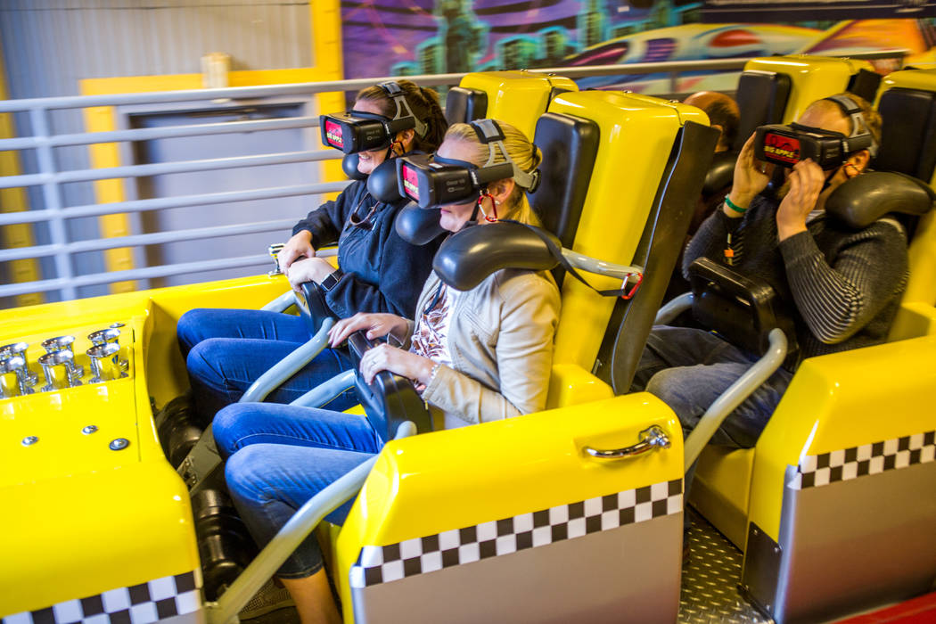 Ashley Day, izquierda, y Amanda Lewis, segunda desde la izquierda, de West Palm Beach, Florida, viajan en Big Apple Coaster con gafas de realidad virtual en el New York-New York, en Las Vegas, el  ...