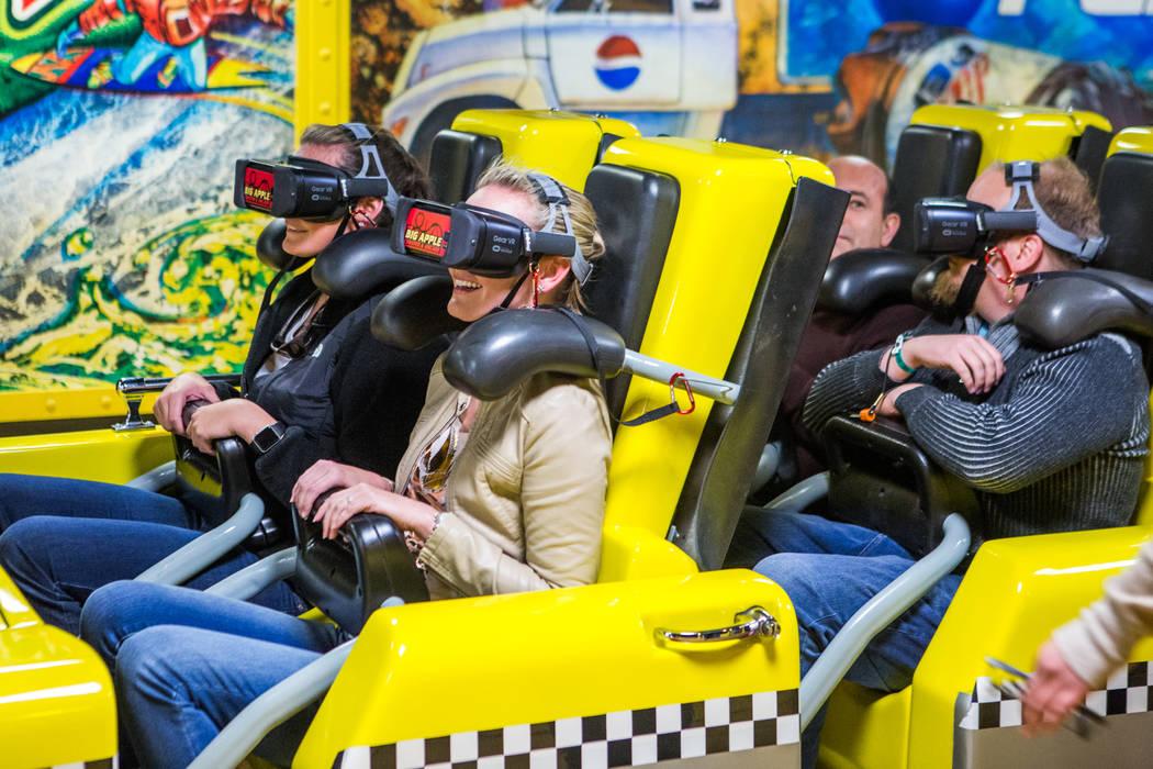 Ashley Day, izquierda, y Amanda Lewis, segunda desde la izquierda, de West Palm Beach, Florida, terminan su recorrido en la Gran Montaña Rusa de la Manzana con gafas de realidad virtual en el New ...