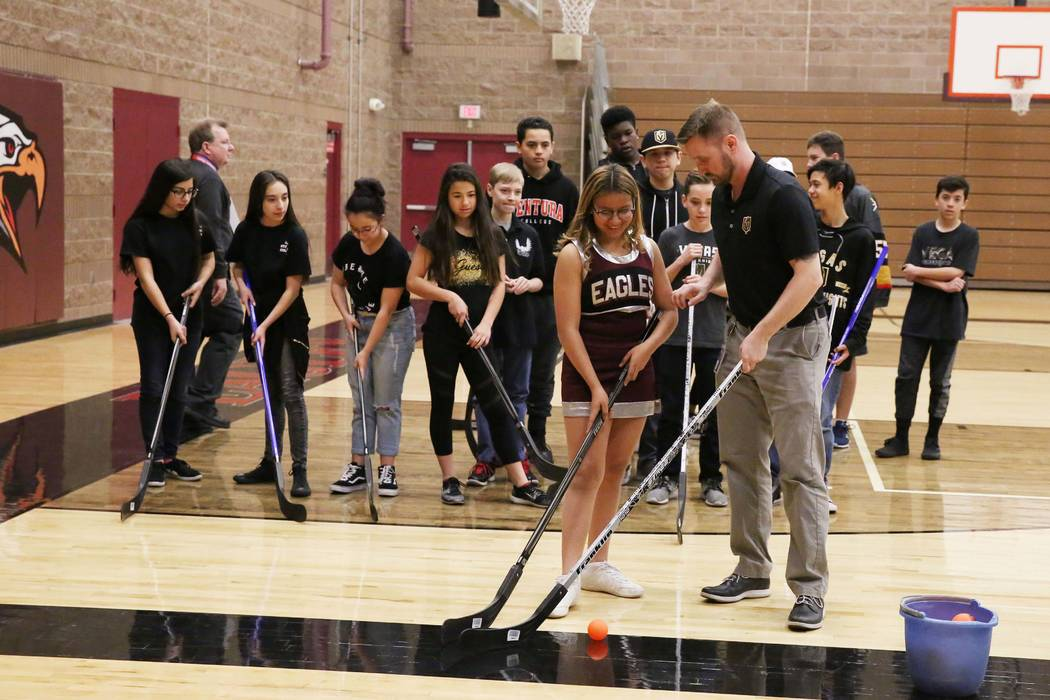Matt Flynn, gerente senior de Vegas Golden Knights, hockey juvenil, derecha, demuestra cómo sostener un palo de hockey con Evelyn Murillo en la escuela secundaria Walter Johnson el lunes 12 de fe ...