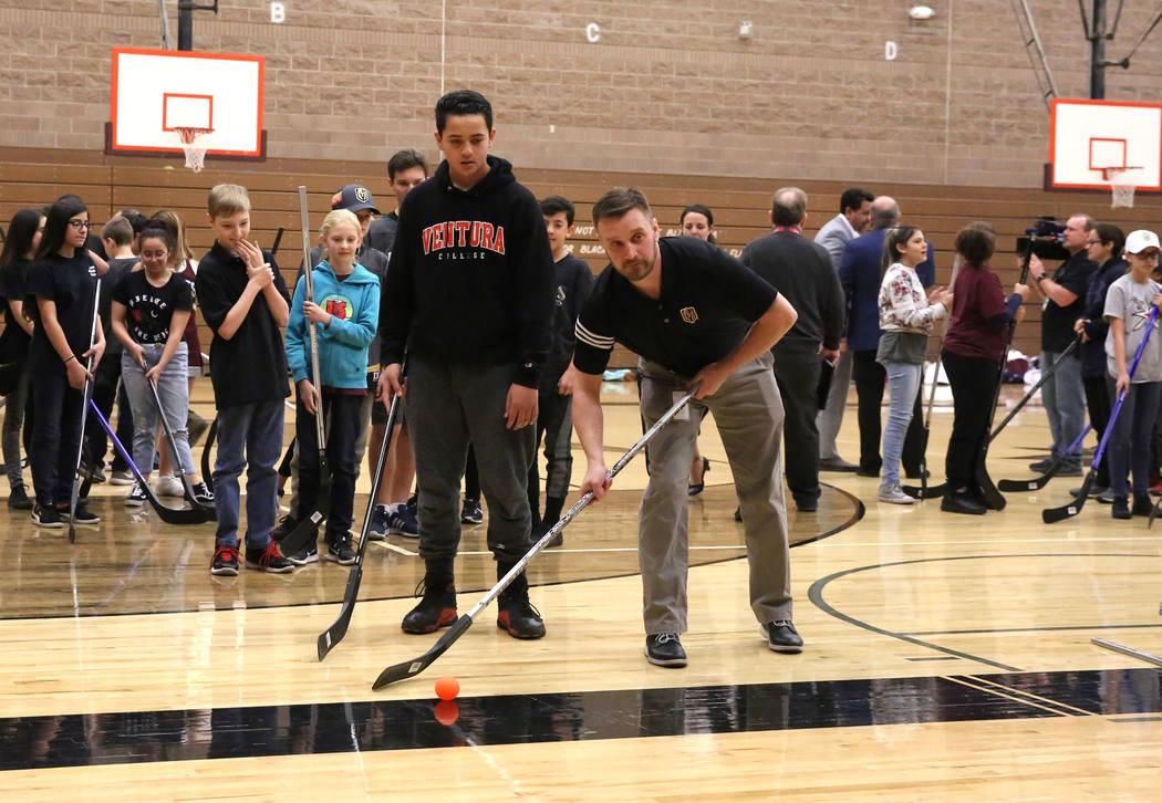 Matt Flynn, gerente senior de Vegas Golden Knights, hockey juvenil, derecha, demuestra cómo golpear el objetivo a Maddox Valoaga en la Junior High School Walter Johnson el lunes 12 de febrero de  ...