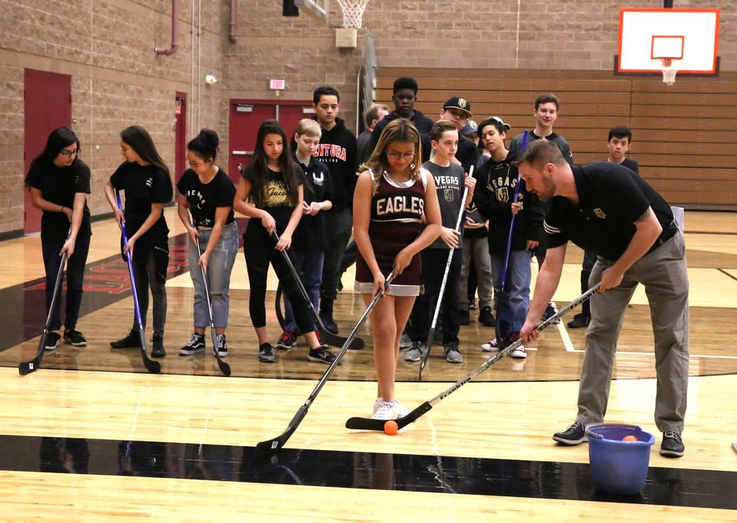 Matt Flynn, gerente senior de Vegas Golden Knights, hockey juvenil, derecha, demuestra cómo golpear el objetivo a Evelyn Murillo en la escuela secundaria Walter Johnson el lunes 12 de febrero de  ...