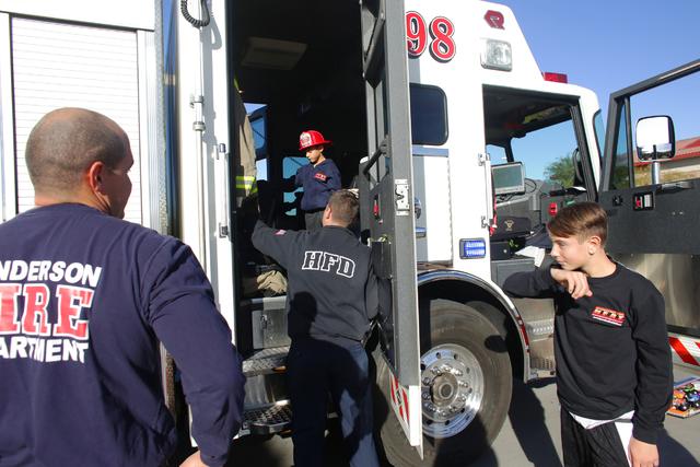 El bombero Donovan Kutsenda le da a Edward Angulo, de 6 años, y Chance Harridge, de 12, un recorrido por el camión de bomberos en la Estación de Bomberos 98, el martes 20 de diciembre de 2016,  ...