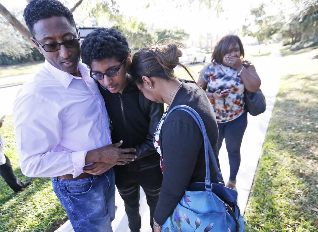 Los familiares se abrazan después de que algún estudiante saliera de Marjory Stoneman Douglas High School el miércoles 14 de febrero de 2018 en Parkland, Florida. Los disparos en la escuela sec ...