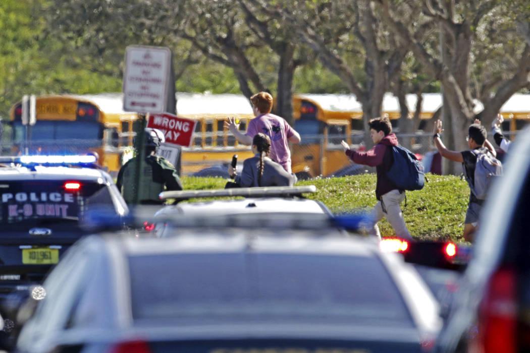 Los estudiantes corren con las manos en el aire después de un tiroteo en Marjory Stoneman Douglas High School en Parkland, Fla., El miércoles, 14 de febrero de 2018. (John McCall / South Florida ...
