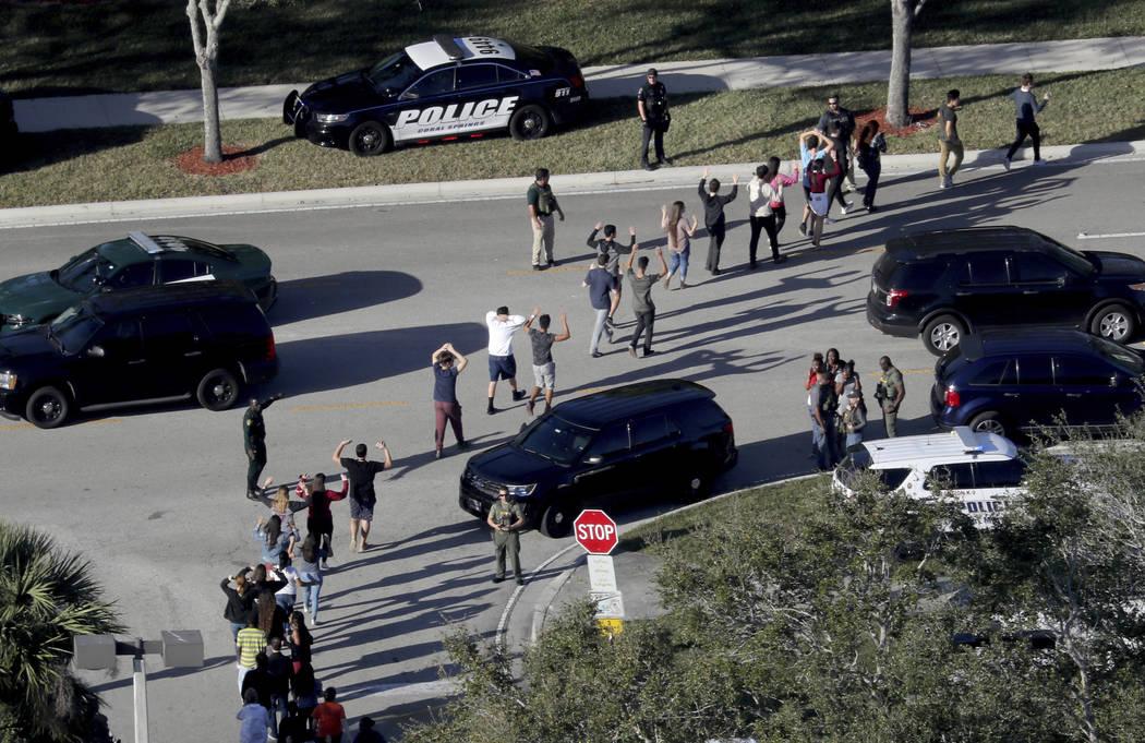Los estudiantes sostienen sus manos en el aire mientras son evacuados por la policía de Marjorie Stoneman Douglas High School en Parkland, Fla., Después de que un tirador abrió fuego en el camp ...