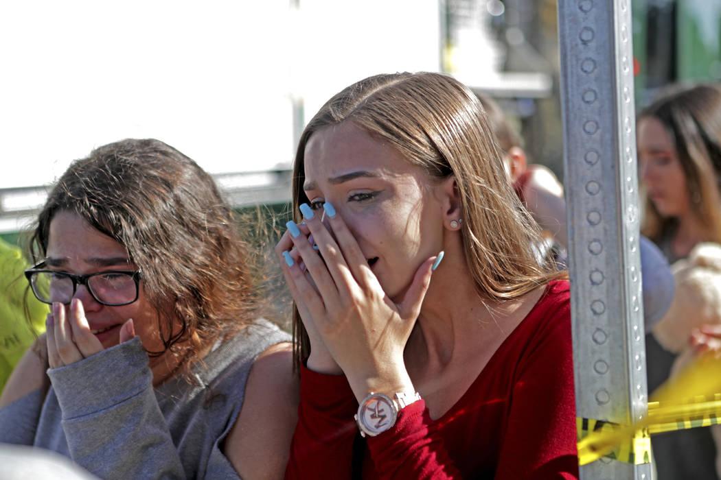 Los estudiantes liberados de un encierro se muestran llenos de emoción después de un tiroteo en Marjory Stoneman Douglas High School en Parkland, Fla., El miércoles, 14 de febrero de 2018. (Joh ...
