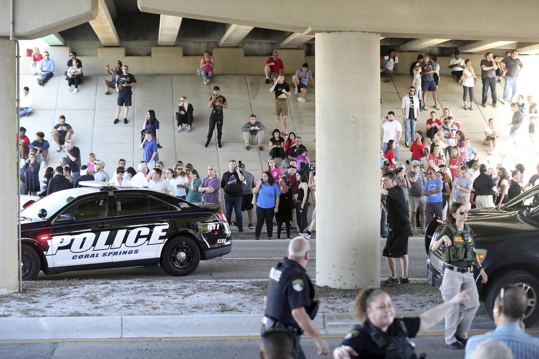 A la espera de noticias de los padres y las familias de los estudiantes, se reúnen en Coral Springs Drive y Sawgrass Expressway justo al sur del campus después de un tiroteo en Marjory Stoneman  ...