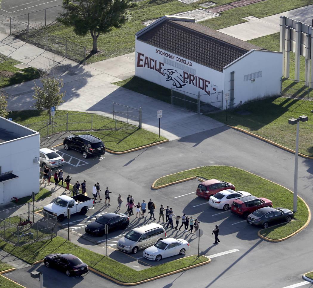 Los estudiantes son evacuados por la policía de la escuela preparatoria Marjory Stoneman Douglas en Parkland, Fla., El miércoles 14 de febrero de 2018, después de que un tirador abrió fuego co ...