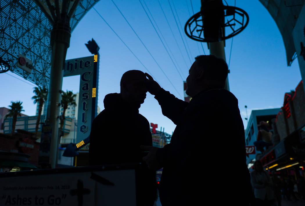 Steve Willis, pastor principal de la Iglesia First Christian, a la derecha, marca la frente del obispo Williams de Las Vegas el miércoles de ceniza en la calle Fremont, en el centro de Las Vegas, ...