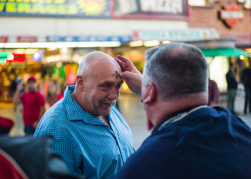 Steve Willis, pastor principal de la Iglesia First Christian, a la derecha, marca la frente de Frank Cormier de New Brunswick, Canadá, el miércoles de ceniza en la calle Fremont, en el centro de ...