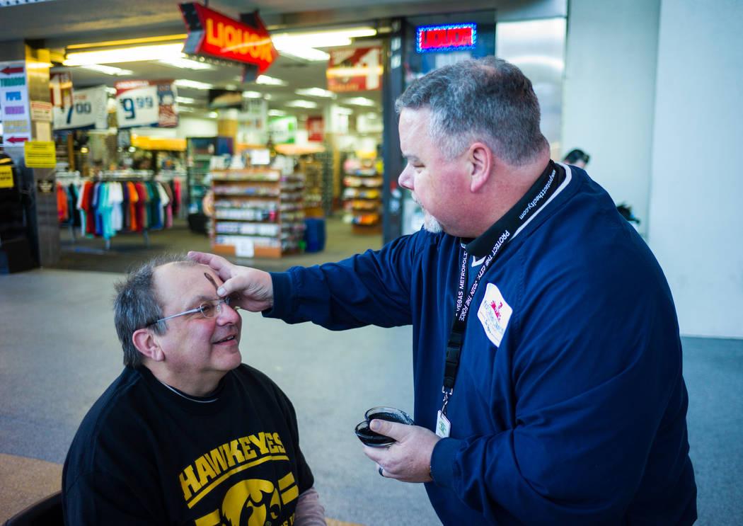 Steve Willis, pastor principal de la Iglesia First Christian, a la derecha, marca la frente de Sam Adam de Iowa City, Iowa, el miércoles de ceniza en la calle Fremont, en el centro de Las Vegas,  ...
