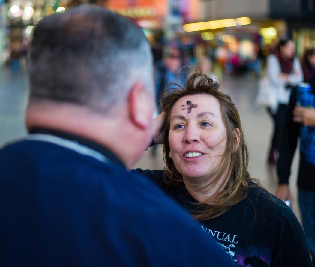 Steve Willis, pastor principal de la Iglesia First Christian, marca la frente de Michelle Caldwell of Ill. Para el Miércoles de Ceniza en la calle Fremont, en el centro de Las Vegas, el miércole ...