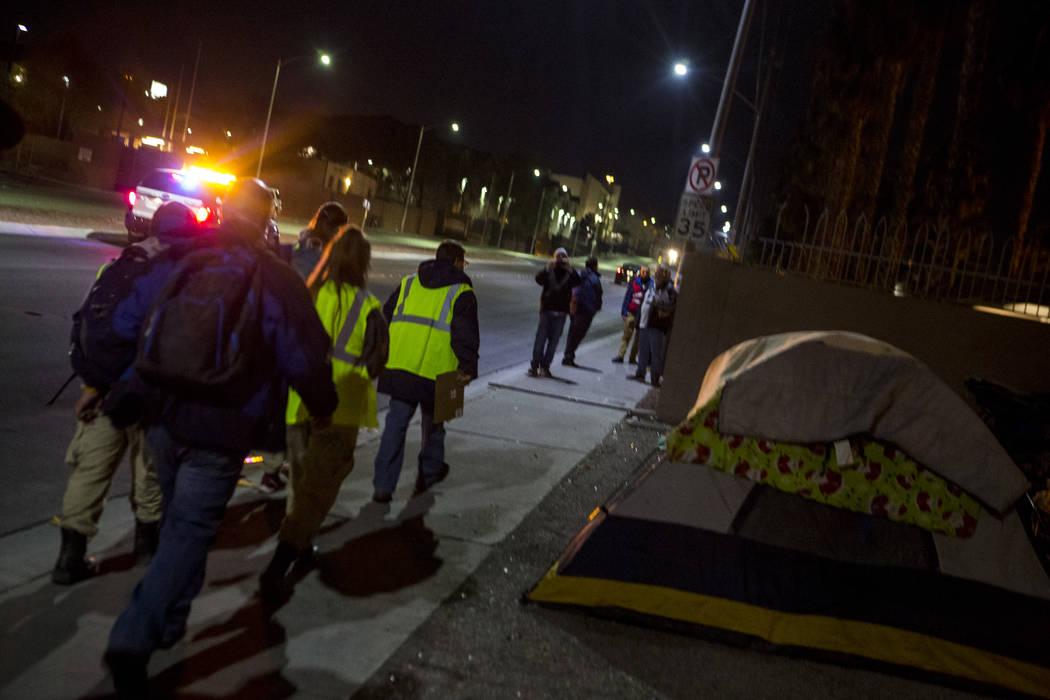 Voluntarios para el censo anual de personas sin hogar del condado de Clark caminan más allá de un campamento en la Avenida Oeste Owens en el Norte de Las Vegas el miércoles, 24 de enero de 2018 ...