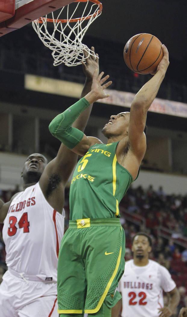 Elijah Brown de Oregón enfrenta a Terrell Carter II del Estado de Fresno en la primera mitad de un juego de baloncesto universitario de la NCAA en Fresno, California, el sábado 16 de diciembre d ...