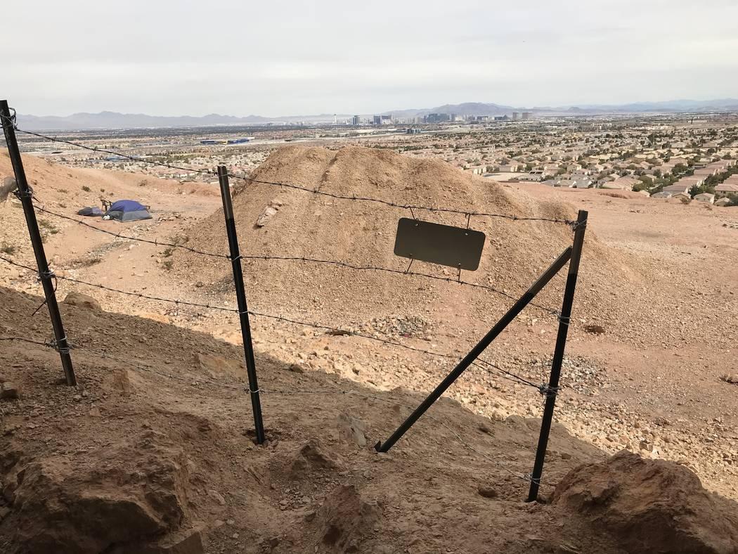 Una valla de alambre de púas bloquea parcialmente una entrada de mina abandonada que pronto será rellenada cerca de las carreteras de Fort Apache y Warm Springs el miércoles 21 de febrero de 20 ...