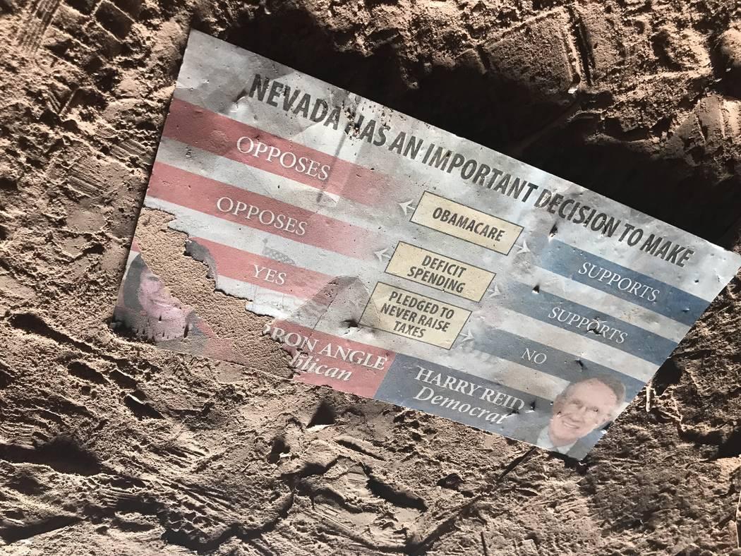 Un anuncio de campaña desde el 2010 del senador Harry Reid recoge polvo en el piso de un pozo de mina abandonado cerca de las carreteras de Fort Apache y Warm Springs el miércoles 21 de febrero  ...
