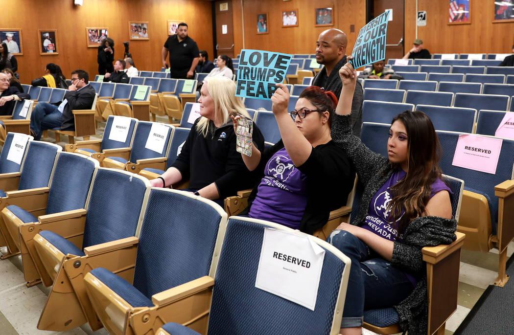 Laura Hernández, centro, y Kristina Hernández, derecha, mantienen sus carteles en alto después de que la mayoría de la multitud se fue después de la decisión de la Junta Escolar del Condado  ...