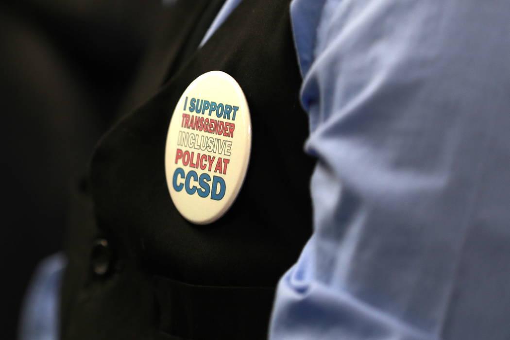 Un asistente usa un alfiler en apoyo de una política de género durante una reunión de la Junta Escolar del Condado de Clark, que finalizó con el retiro de la polémica política de la agenda,  ...