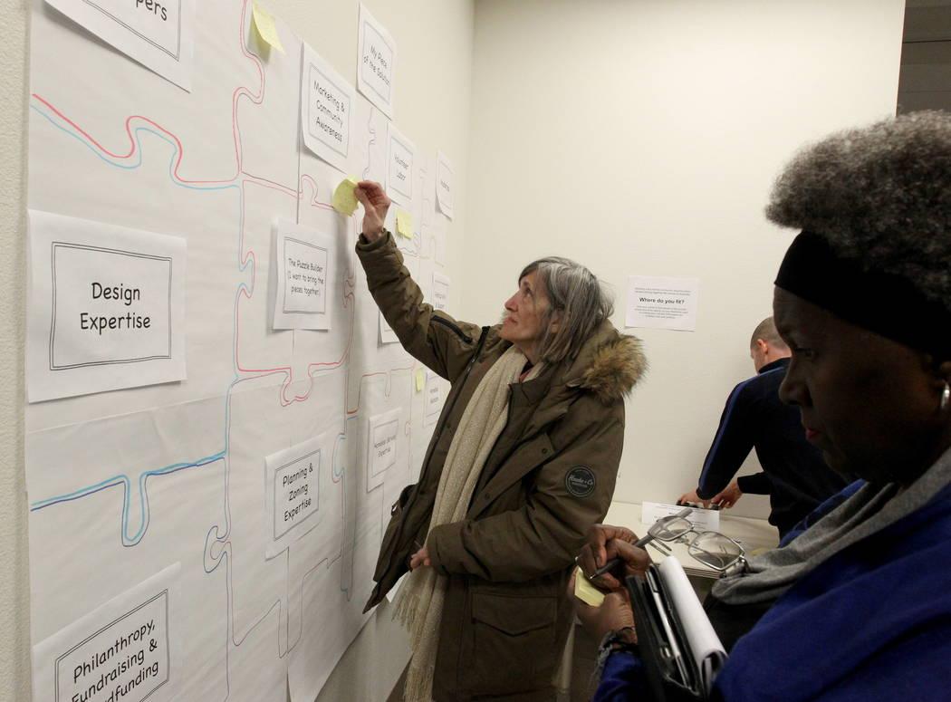 Marian Luke aplica notas Post-it a un rompecabezas con una oferta para ofrecerse como voluntario para ayudar a resolver la falta de vivienda durante la Iniciativa de Fe del Alcalde Tiny Home micro ...