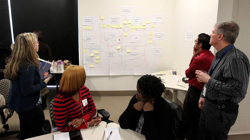 La gente leyendo notas de Post-it destinadas a completar las piezas del rompecabezas para ayudar a resolver la falta de vivienda durante la Iniciativa de Fe del Alcalde Tiny Home micro Summit en e ...