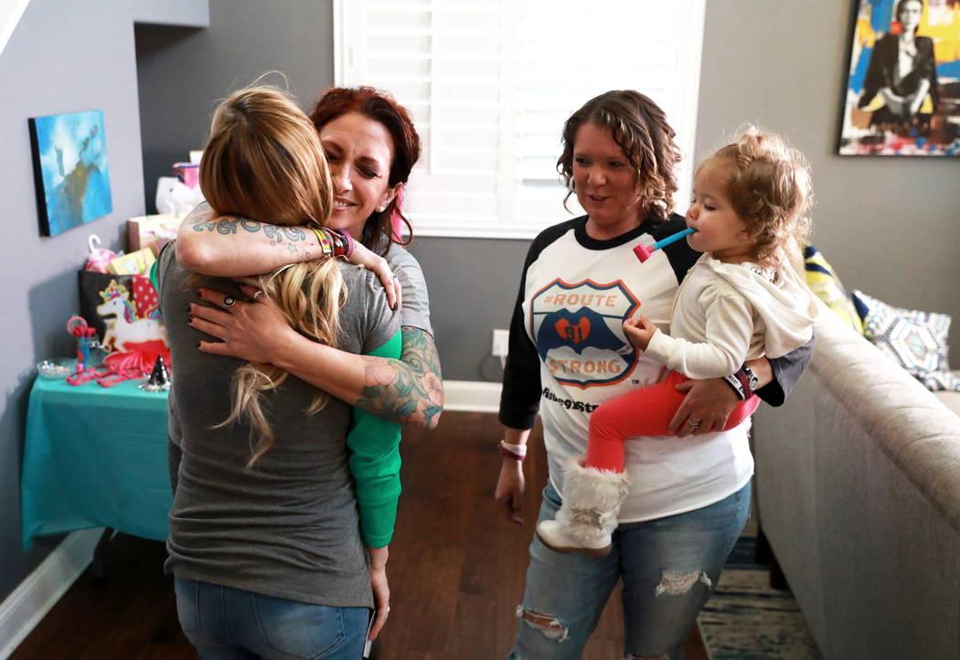 La sobreviviente de Route 91 Mindy Foster abraza a Colie Knoke, otra sobreviviente, mientras Jennifer Holub lleva a Aubri, la hija de Knoke de 2 años, después de recibir un cheque de la Route91  ...