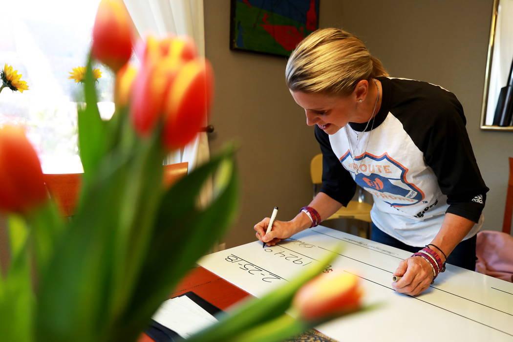 Lisa Fine, sobreviviente del tiroteo y fundadora de Route 91 Strong, firma un cheque para los sobrevivientes del tiroteo del 1 de octubre en Las Vegas el domingo 25 de febrero de 2018. Revista-Dia ...