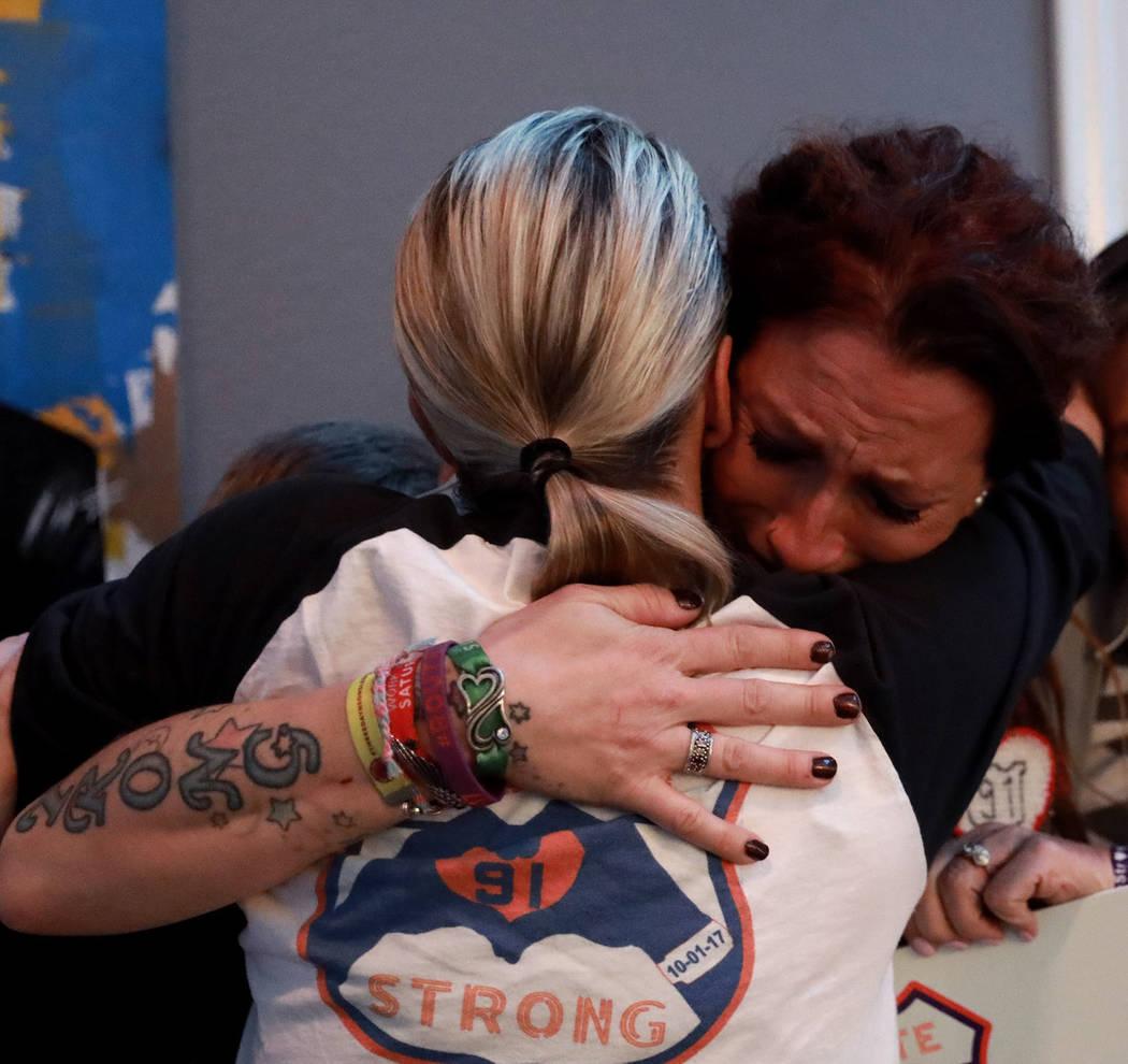 La sobreviviente de la Ruta 91 Mindy Foster, frente a la cámara, abraza a Lisa Fine, otra superviviente y fundadora de Route 91 Strong, después de recibir un cheque de su organización sin fines ...