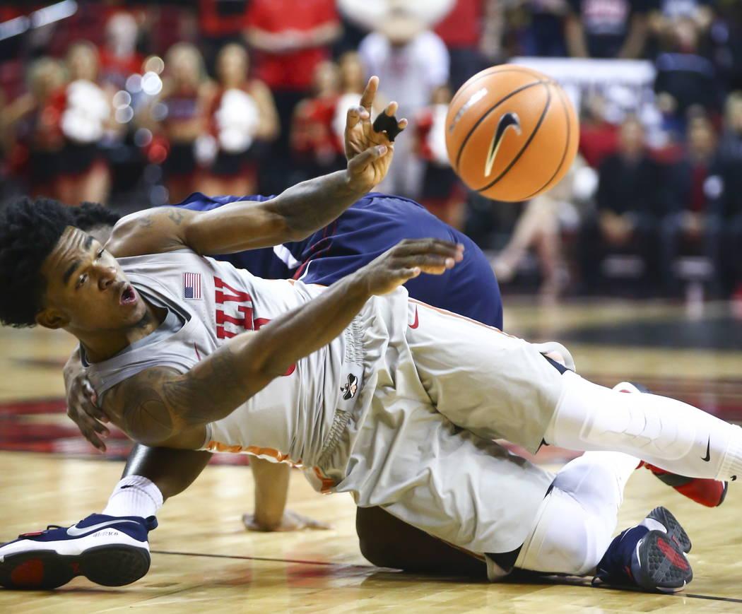 El guardia de UNLV Rebels Jovan Mooring (30) pasa el balón mientras cae al suelo durante la primera mitad de un partido de baloncesto contra los Bulldogs del Estado de Fresno en el Centro Thomas  ...