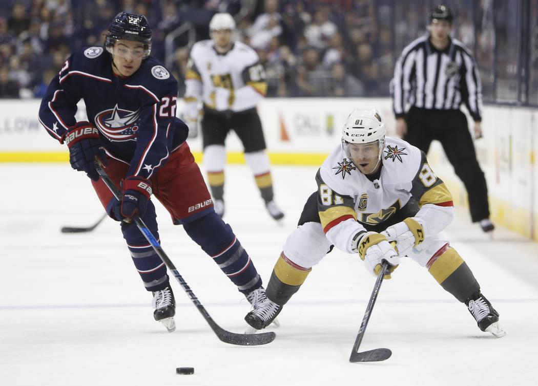 Jonathan Marchessault de Los Angeles Golden Knights, a la derecha, tira el disco más allá de Sonny Milano de Columbus Blue Jackets durante el primer periodo de un juego de hockey de la NHL el ma ...