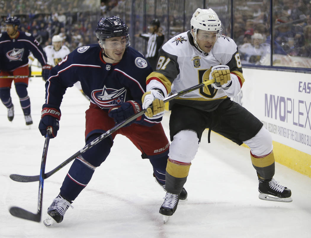 Zach Werenski de Columbus Blue Jackets, izquierda, y Jonathan Marchessault de Los Vegas Golden Knights luchan por una posición durante el primer periodo de un juego de hockey de la NHL el martes  ...