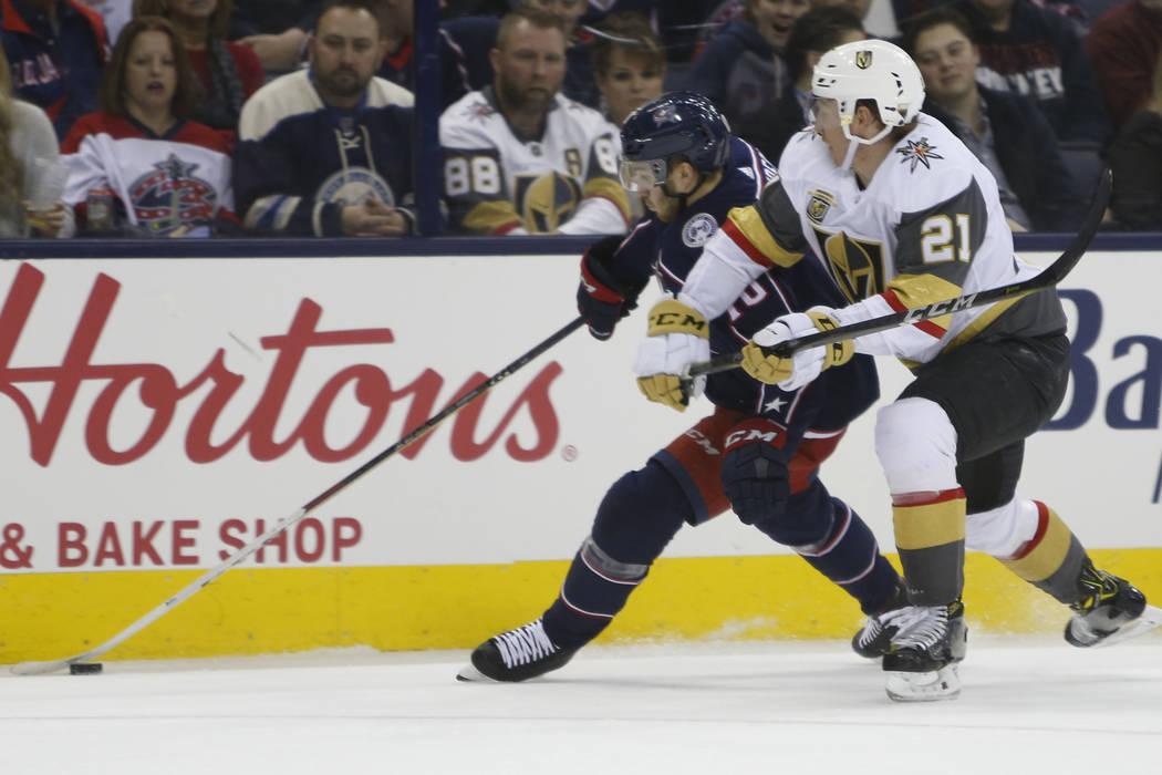 Alexander Wennberg de Columbus Blue Jackets, izquierda, y Cody Eakin de los Golden Knights de Las Vegas persiguen el disco durante el segundo periodo de un juego de hockey de la NHL el martes 6 de ...