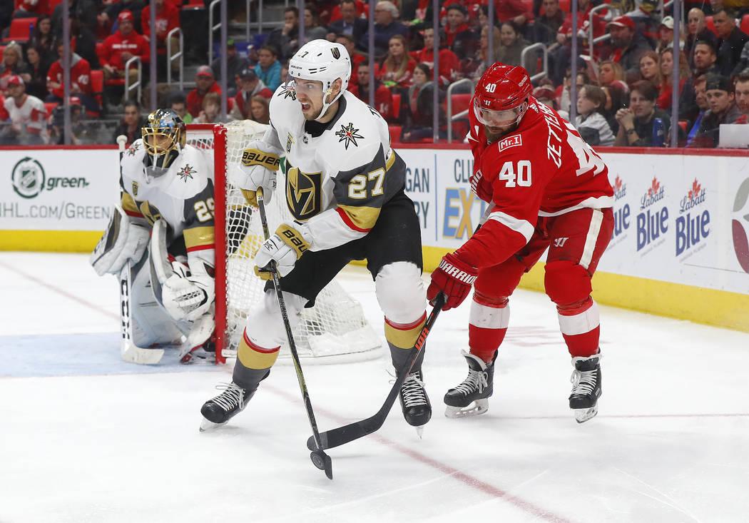 El centro Henrik Zetterberg (40) de Detroit Red Wings levanta el disco del defensor de los Golden Knights de Las Vegas, Shea Theodore (27) en el segundo periodo de un juego de hockey de la NHL el  ...