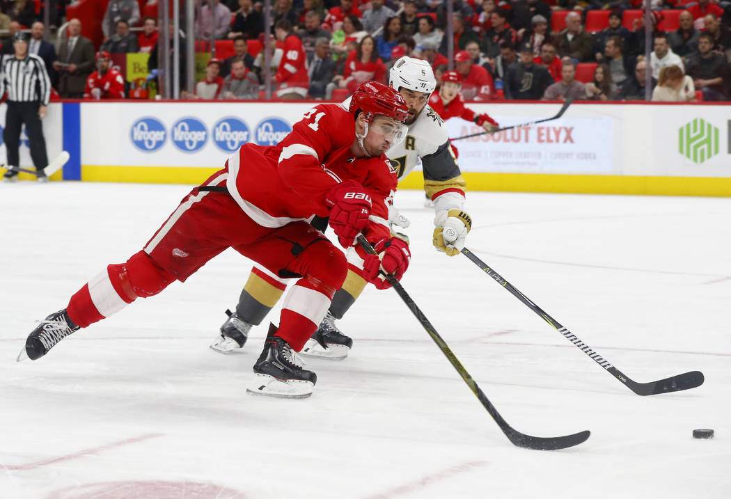 El centro de Detroit Red Wings, Dylan Larkin (71) dispara contra el defensa Deryk Engelland (5) de los Golden Knights durante el segundo periodo de un juego de hockey de la NHL el jueves 8 de marz ...