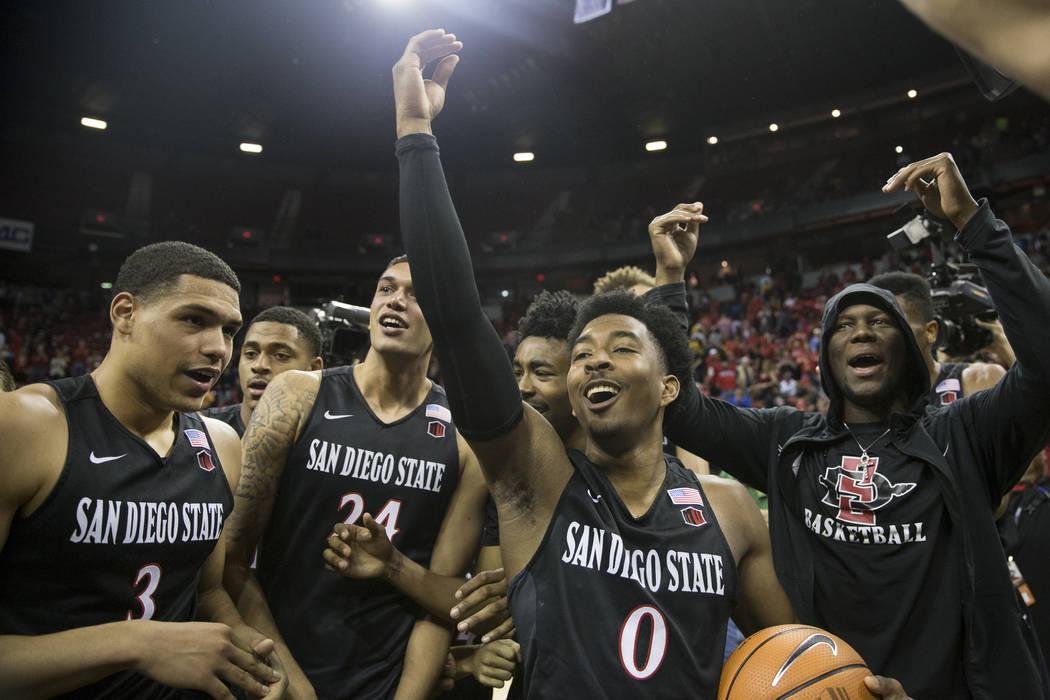 El guardia de San Diego State Aztecs, Trey Kell (3), el alero Nolan Narain (24) y el guardia Devin Watson (0), celebran su victoria en la final del torneo de baloncesto masculino Mountain Conferen ...