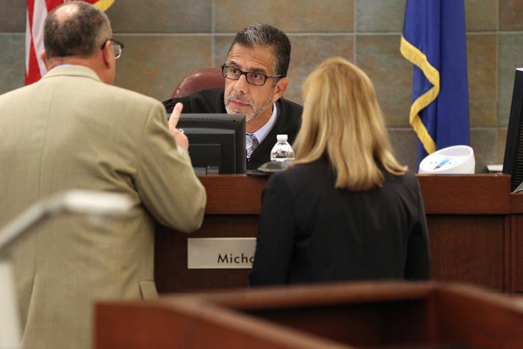 El juez de distrito: Michael Villani, centro, habla con el defensor público adjunto: Bryan Cox, izquierda, y la vicefiscal de distrito Karen Mishler durante la sentencia por inhabilitar al abogad ...