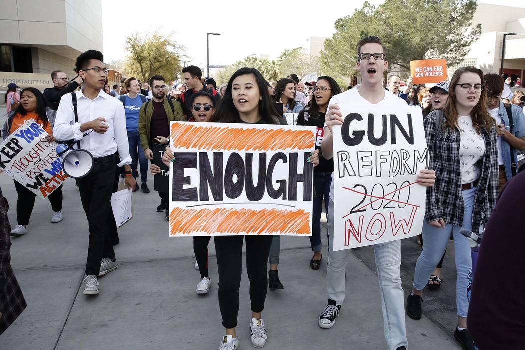 Los estudiantes de la UNLV, incluidos Karl Catarata, segundo a la izquierda, Tiffany Alm, centro, y Aron Csiki gritan consignas mientras marchan en el campus en Las Vegas el miércoles 14 de marzo ...