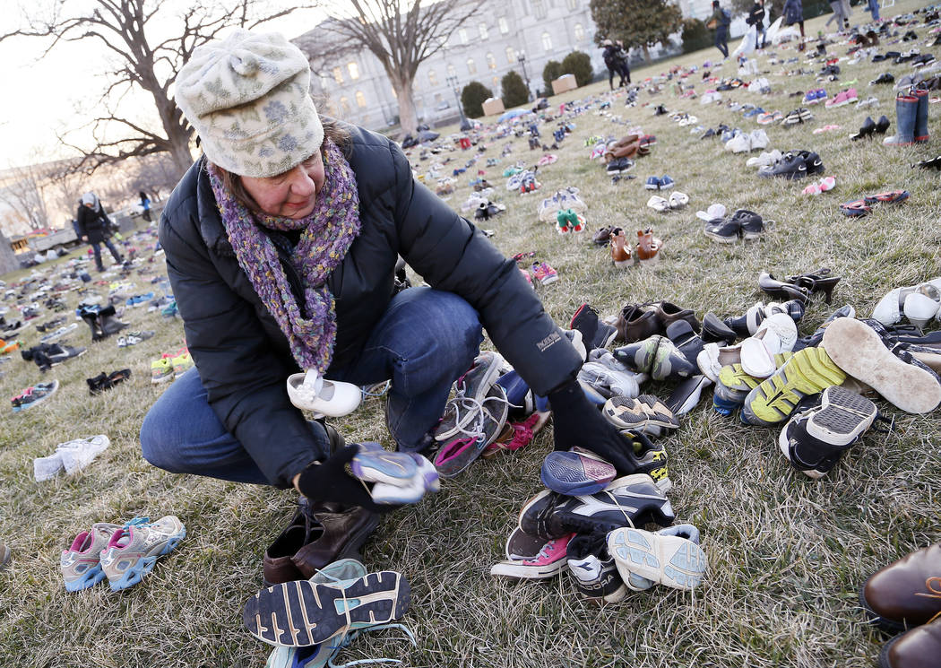 IMAGEN DISTRIBUIDA PARA AVAAZ - Un voluntario establece 7 mil pares de zapatos vacíos por cada niño asesinado con armas en los Estados Unidos desde Sandy Hook en el Capitolio de los EE. UU. El m ...