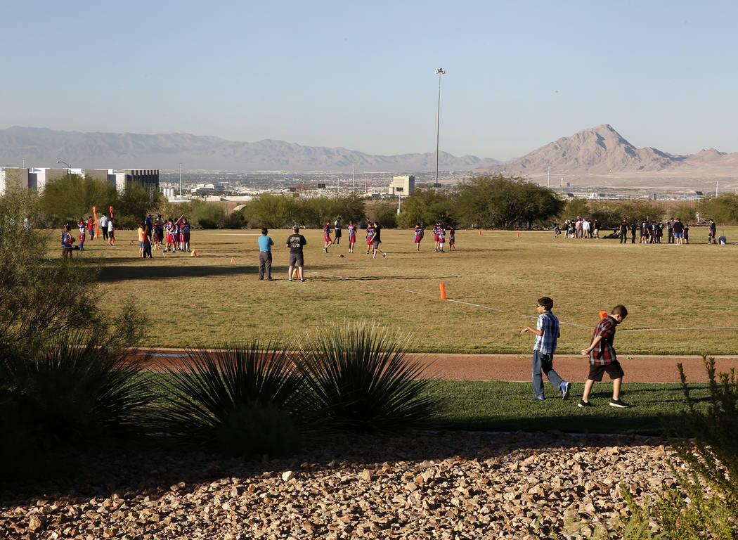 Los niños juegan fútbol americano en el campo detrás de Reunion Trails Park el jueves, 26 de octubre de 2017, en Henderson. La ciudad de Henderson y el Distrito del Condado de Clark están en d ...