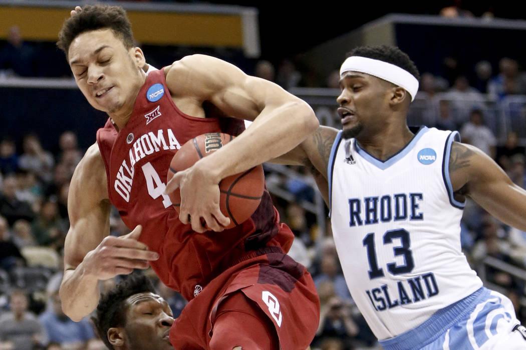 Jamuni McNeace de Oklahoma (4) atrapa un rebote frente a Stanford Robinson de Rhode Island (13) durante la primera mitad en la primera ronda del torneo de baloncesto universitario masculino de la  ...