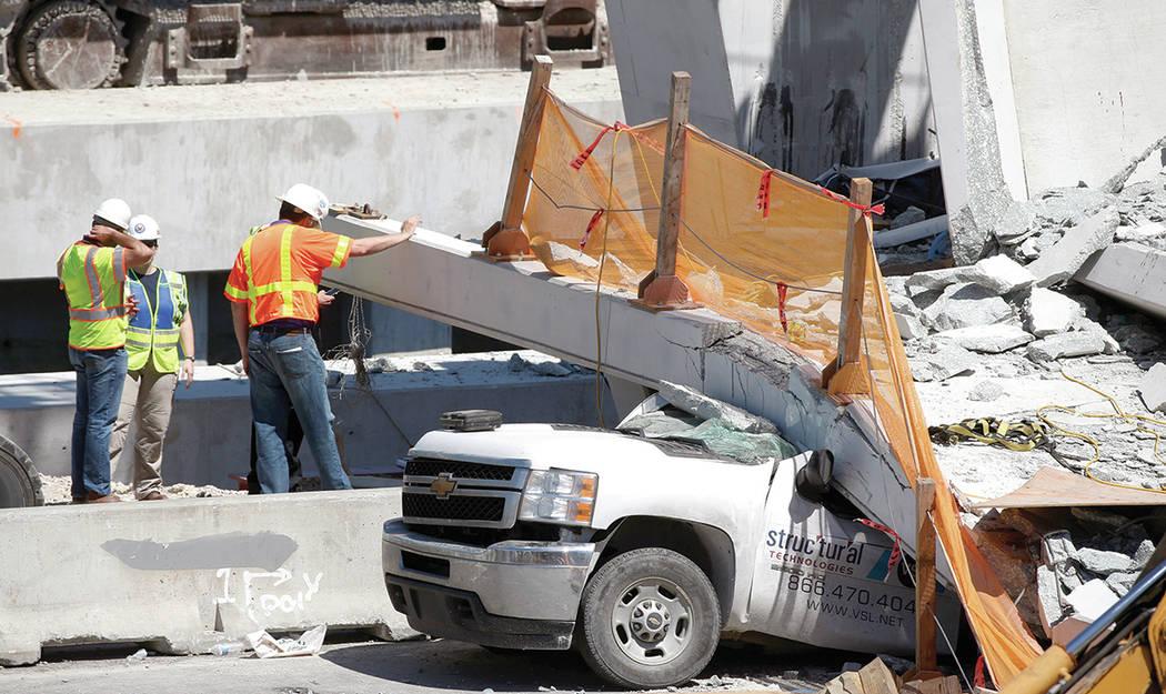 Los trabajadores se paran junto a una sección de un puente peatonal colapsado, el viernes 16 de marzo de 2018 cerca de la Universidad Internacional de Florida en el área de Miami. Un día antes, ...