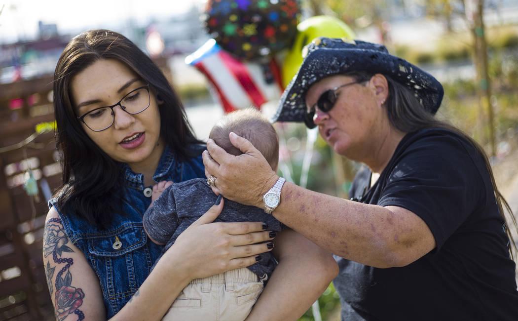 La sobreviviente de disparos: Sue Ann Cornwell, derecha, habla con el infante Xander Finch cuya madre Miriam Lujan, a la izquierda, fue rescatada por Cornwell en el festival Route 91, mientras vis ...